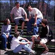 [Five students conversing on a bench]
